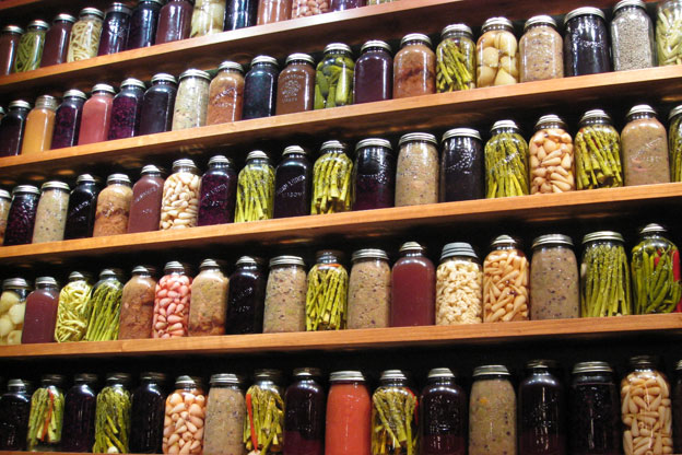 a wall of shelves filled with canned vegetables in glass jars