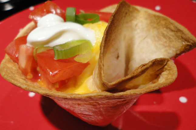 baked tortilla shell with eggs, tomatoes, green onions, and sour cream