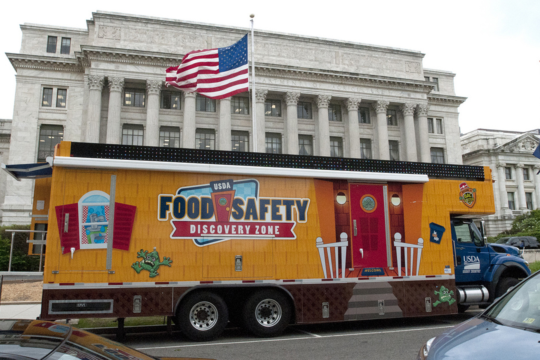 A picture of the Food Safety Discovery Zone, a forty-foot truck that contains an interactive exhibit about food safety.  It is yellow and has a logo on the side. It is in front of the Department of Agriculture building.