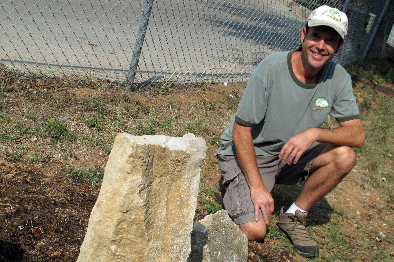 Ferrol Johnson kneels by his garden