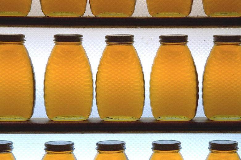 A row of identical honey jars, on a shelf.  They are backlit with a fluorescent light so they glow a bright golden color.