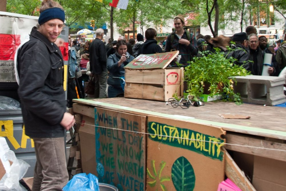 """A man stands beside a makeshift countertop.  Hanging on the side of the counter are posters.  One says """"sustainability"""" with a picture of the earth, and the other reads """"when the wells dry we know the worth of water."""" On top of the counter is a wooden crate for compost. A thick crowd of people mill around in the background. The site is the Occupy Wall Street camp at Zucotti Park."""