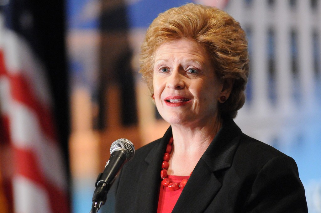 Portrait of Senator Debbie Stabenow, speaking at a microphone.  She is a woman appearing to be in her 50s or 60s, with red hair, wearing a black blazer over a red shirt.  An American flag hangs behind her.