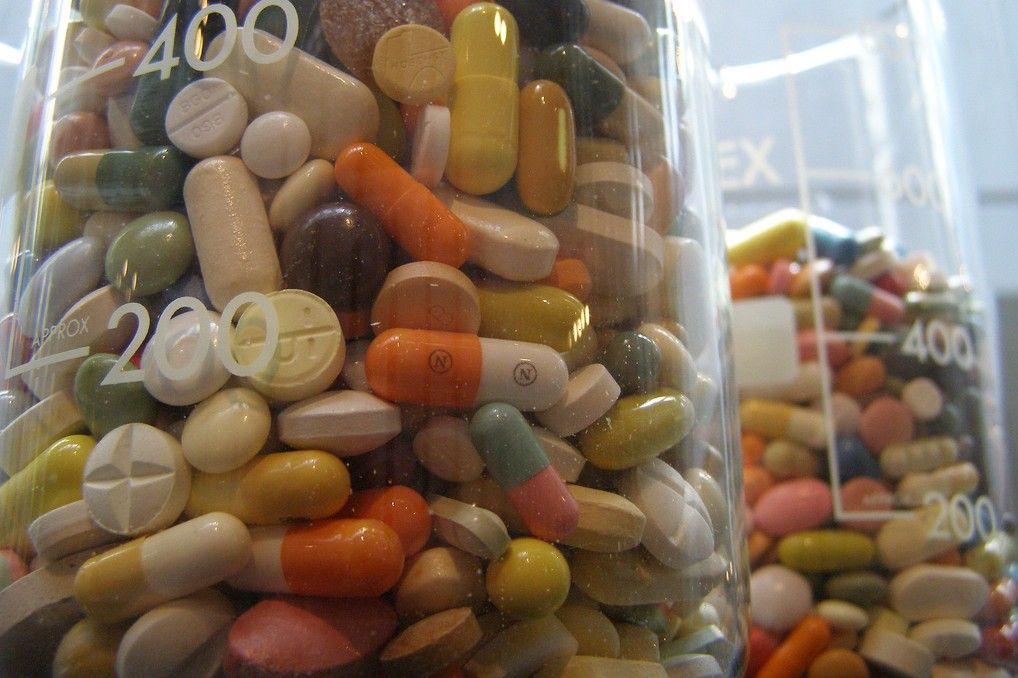 Close-up of two jars full of a variety of multicolored pills.