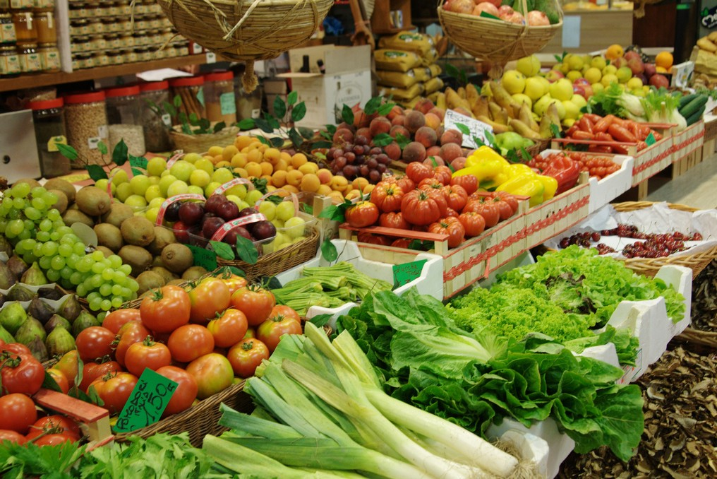 A large spread of fresh produce for sale at a farmer's market, including greens, tomatoes, peppers, and more.