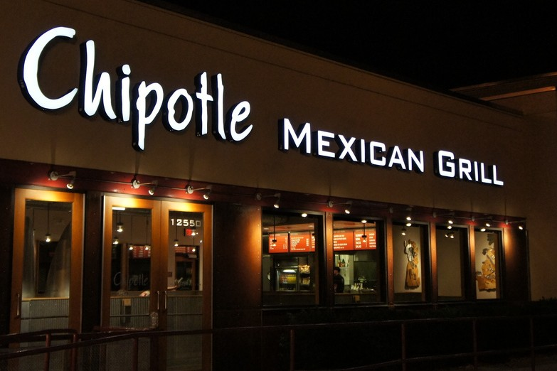 Exterior of a Chipotle Mexican Grill storefront at night.