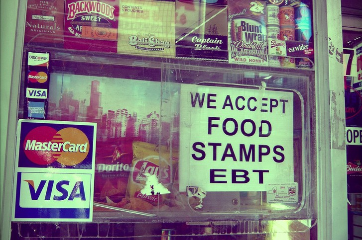"""Close up of a shop window with a sign that says """"We accept food stamps, EBT"""""""