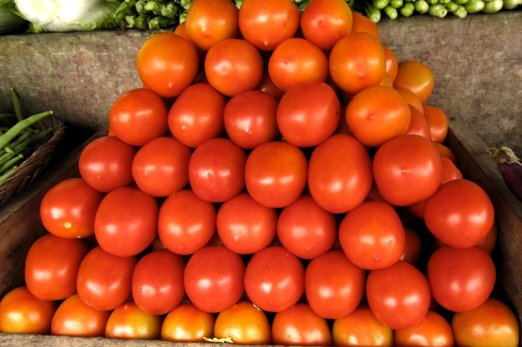A pile of tomatoes stacked like building blocks at a grocery store.