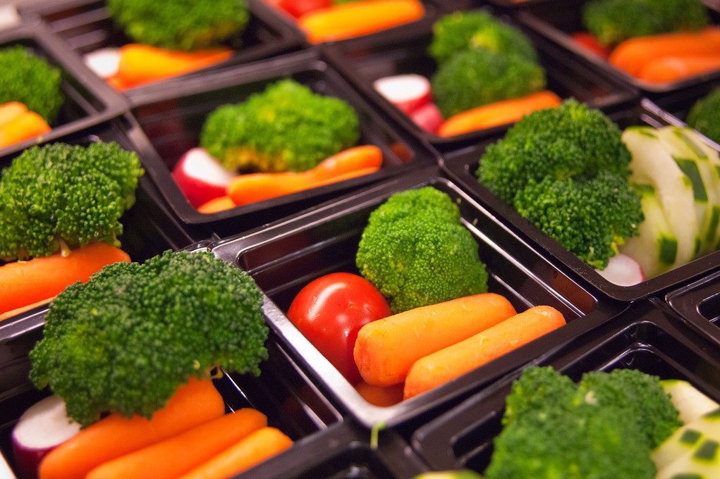 Rows of vegetable servings for school lunches, including broccoli, baby carrots, and radishes.