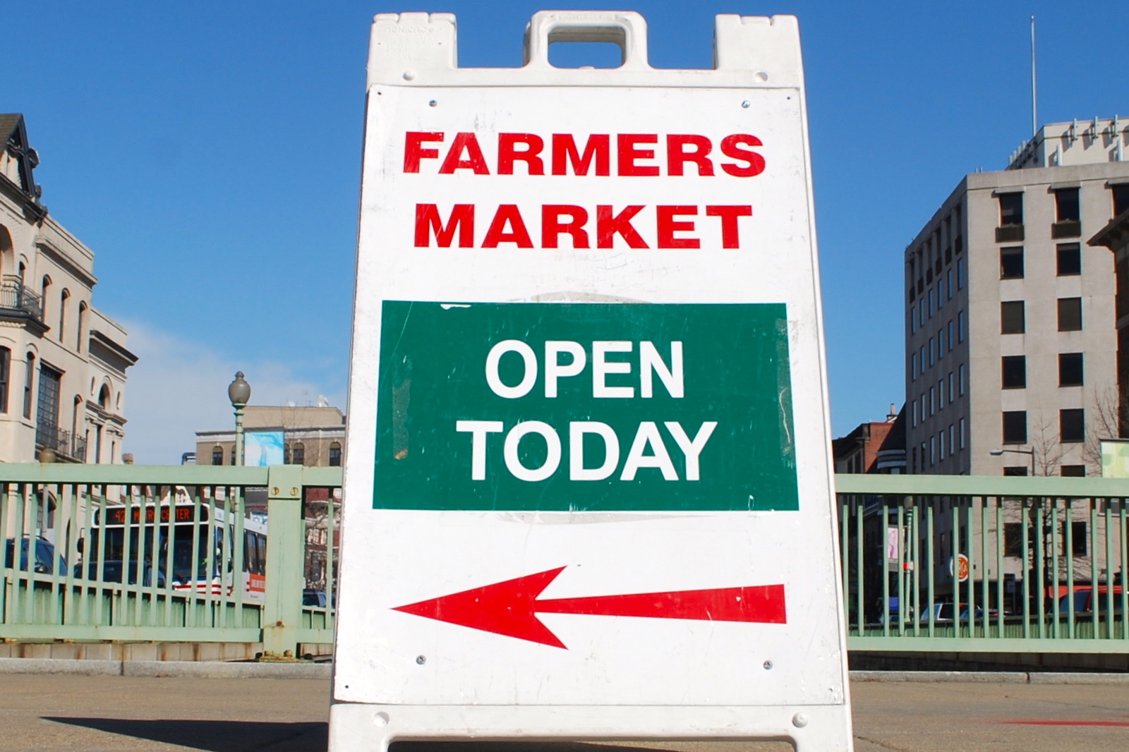 Sign points to open farmers market.