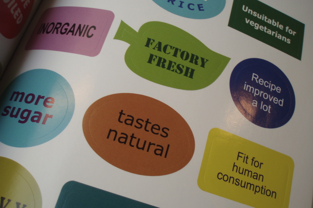 """colorful stickers with phrases such as """"tastes natural"""" and """"factory fresh"""""""