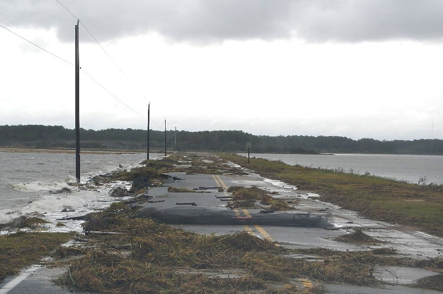 Under a grey sky, a road is covered with debris from the storm.