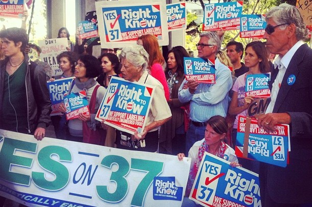 """A group of supporters holding """"Yes On 37 - Right to Know"""" posters stand together at a rally."""