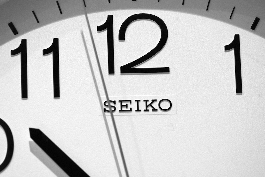 The second hand on an analog clock approaches the 12.