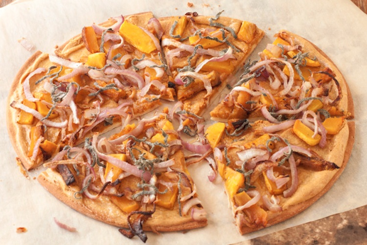 Butternut squash and sage pizza sliced and sitting on a tabletop