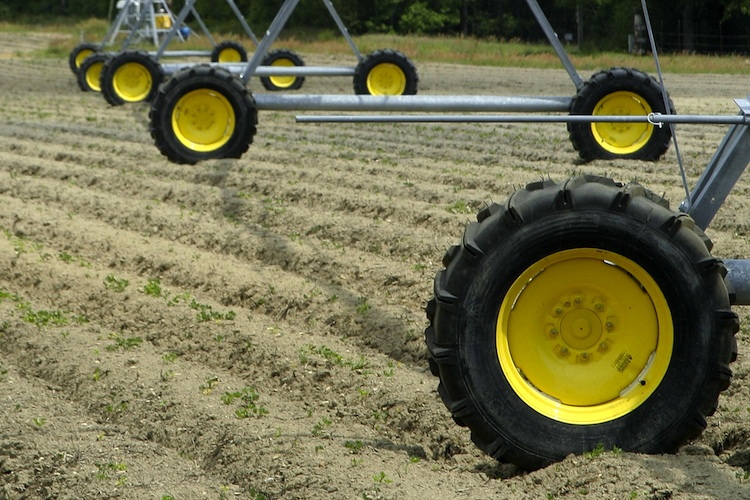 The yellow wheels of a center-pivot irrigation system on tilled farmland