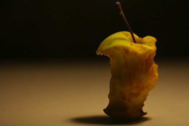 A softly lit apple core against a dark backdrop