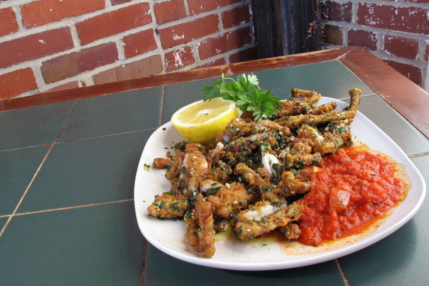 plate of frog legs with tomato sauce