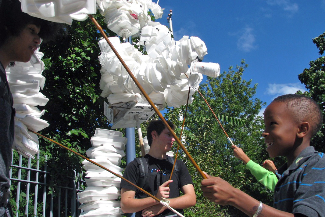 A child works a giant puppet made of styrene foam trays