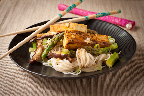 A plate of tofu, noodles, and asparagus