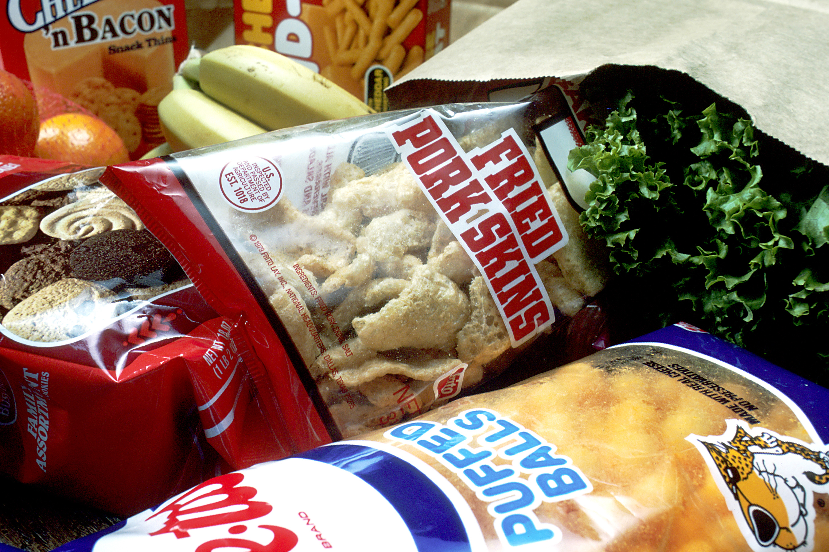 A bag of groceries containing Cheetos, fried pork skins, cookies, cheddar and bacon crackers, bananas, oranges and lettuce.