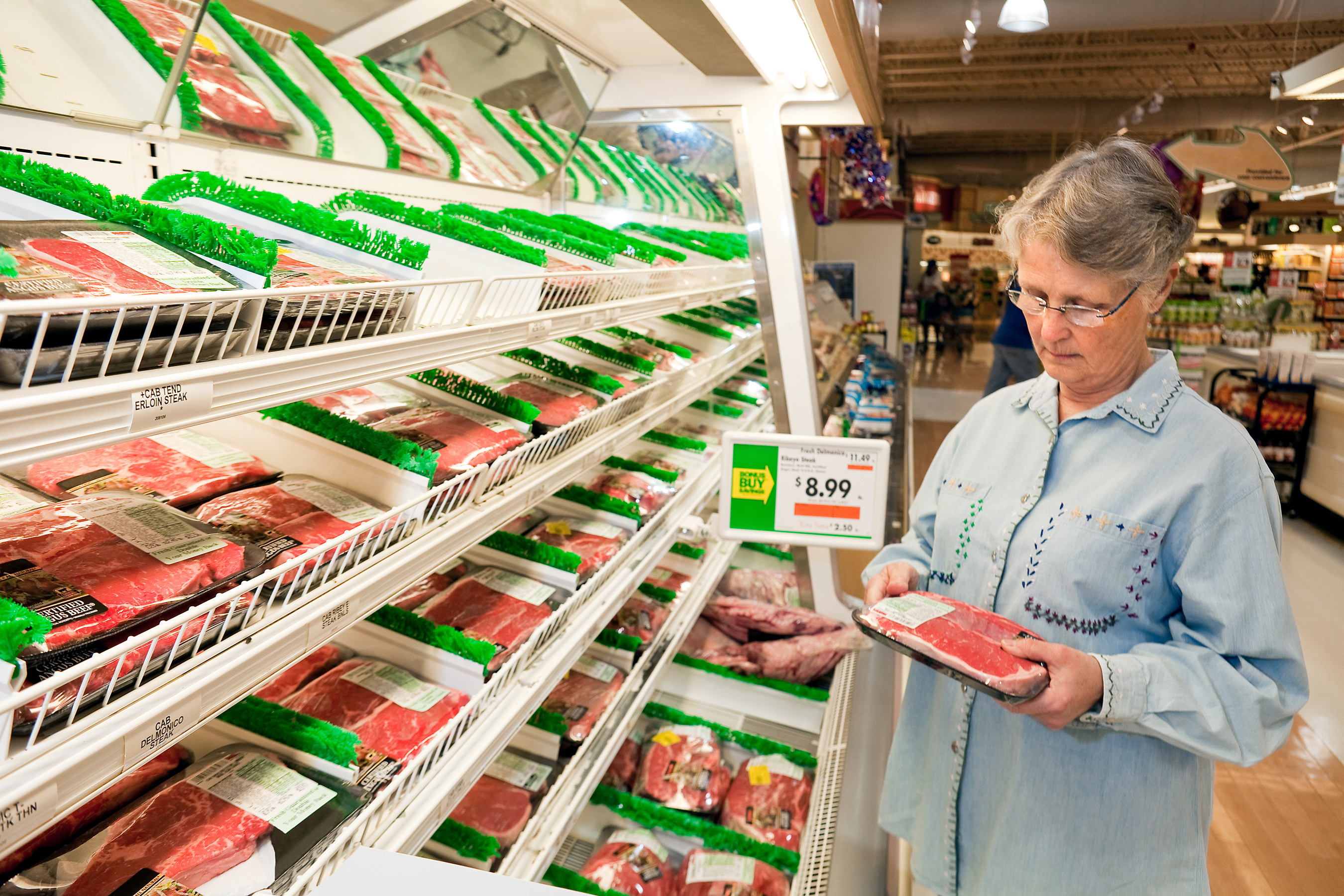 A customer shops for packaged meat at a supermarket