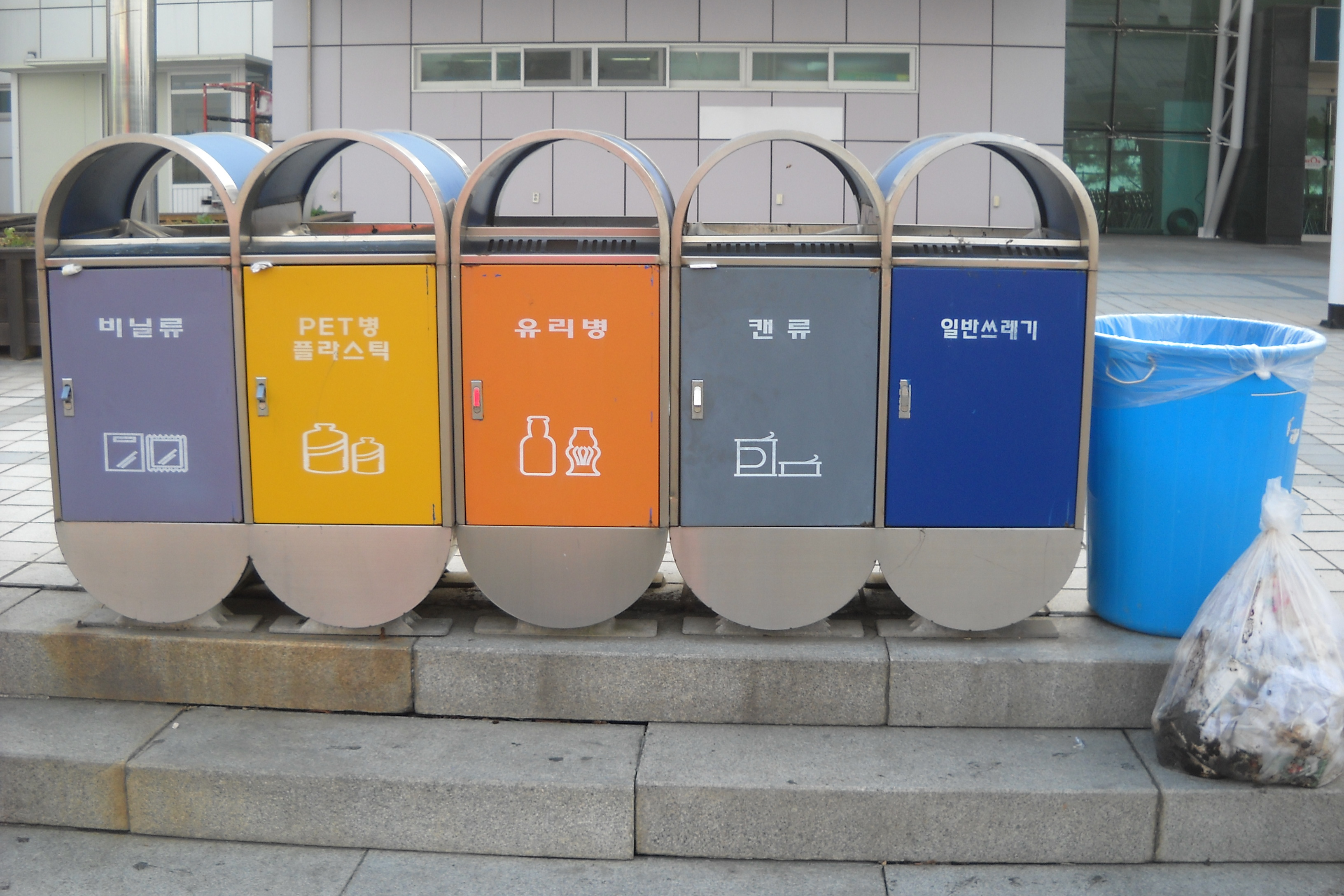 Recycling receptacles line a curb in South Korea