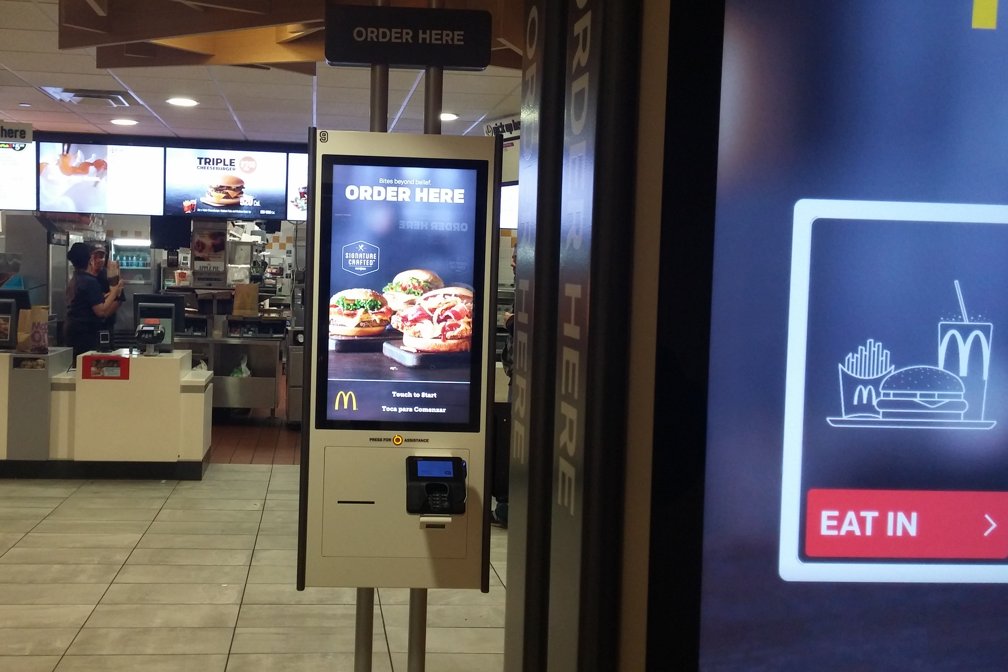 Workers wait at cash registers at a McDonald's restaurant in New York fitted with self-serve kiosks.