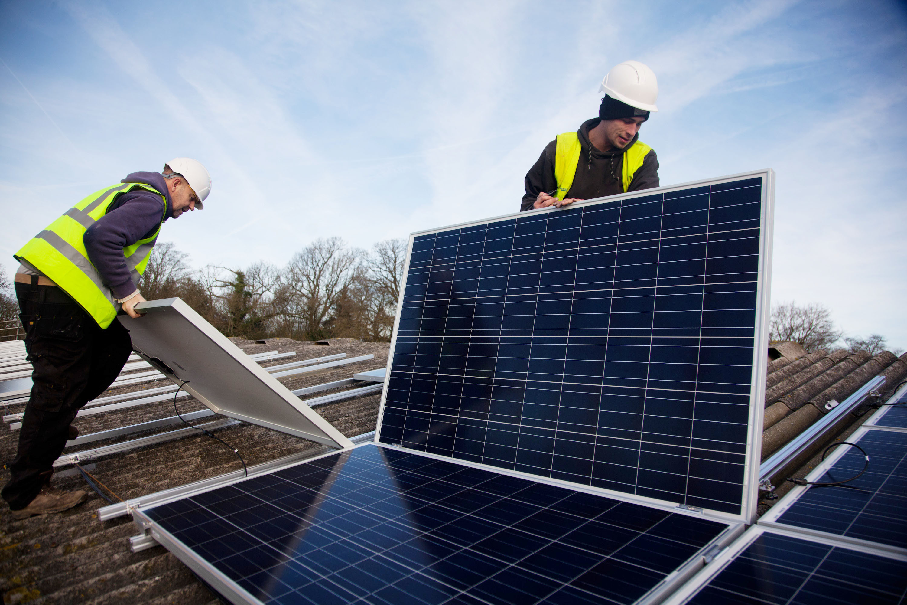 Workers install solar panels on the roof of a barn.