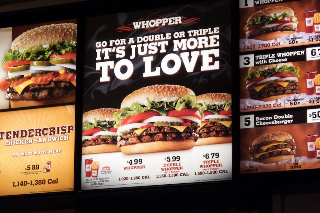 A Burger King sign displays calorie counts