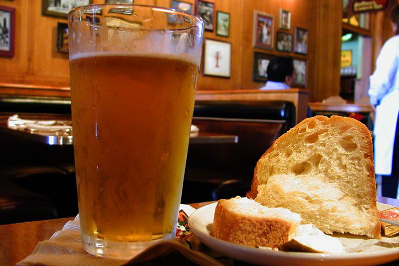 A glass of beer sits next to a bread board at a pub
