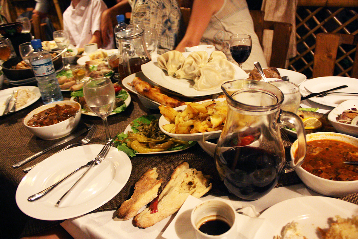 Georgian cuisine includes elaborate banquets called Supras, featuring many dishes, piled high on the table. (Thiery/Flickr)