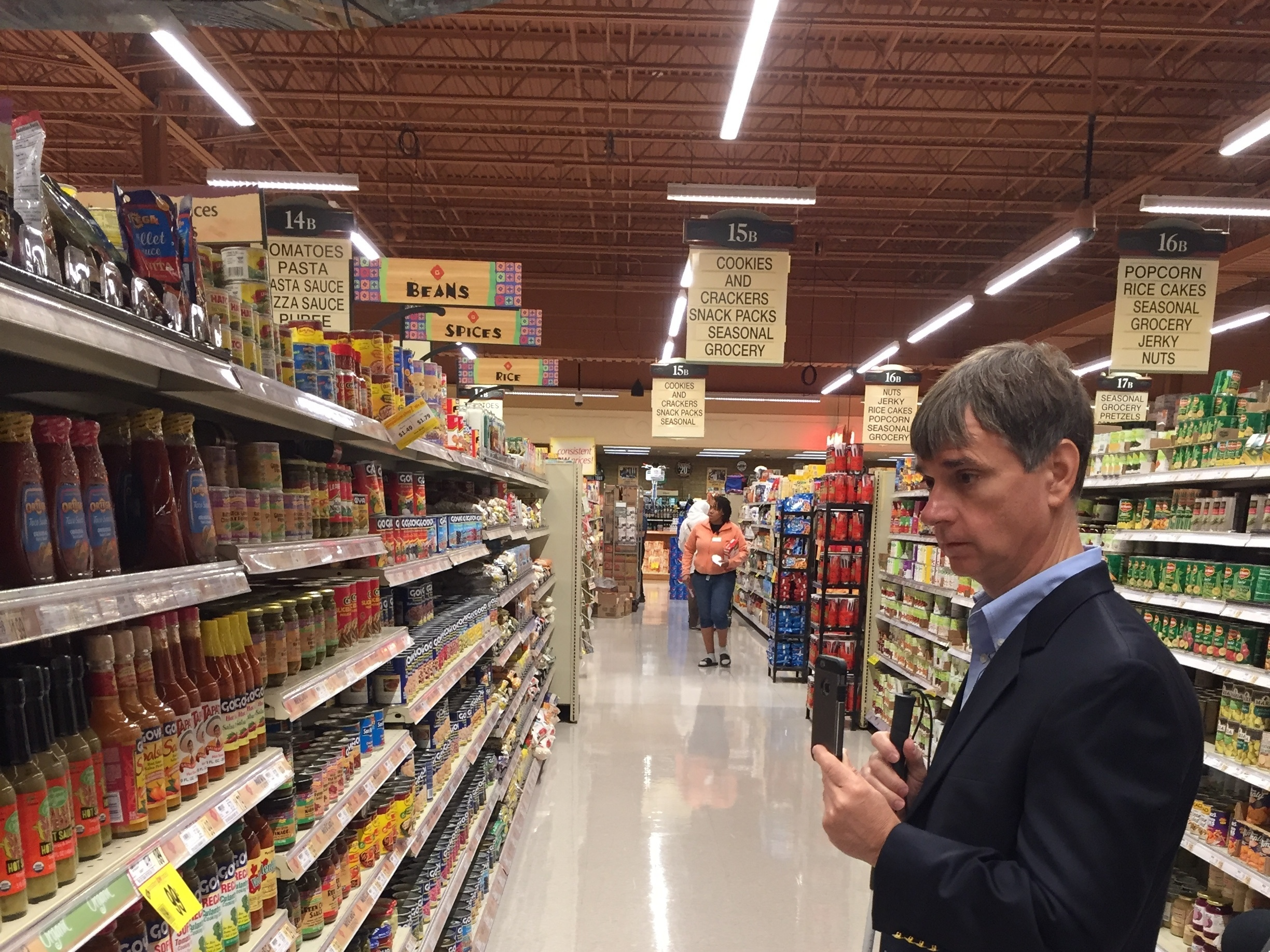 Gary Wagner, a blind Buffalo resident and subscriberto an app that connects him to a shopping assistant, looks for hot sauce at a Wegmans store in Amherst, New York. (Ronald Peralta/WBFO)