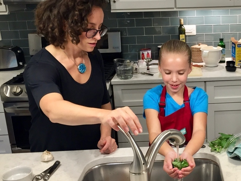 Molly Birnbaum, <em>America's Test Kitchen Kids</em> editor in chief, helps 8-year-old Lucy Gray make a one-pot pasta meal from a recipe in the new book, <em>The Complete Cookbook for Young Chefs</em>. (Courtesy of Paul Gray)