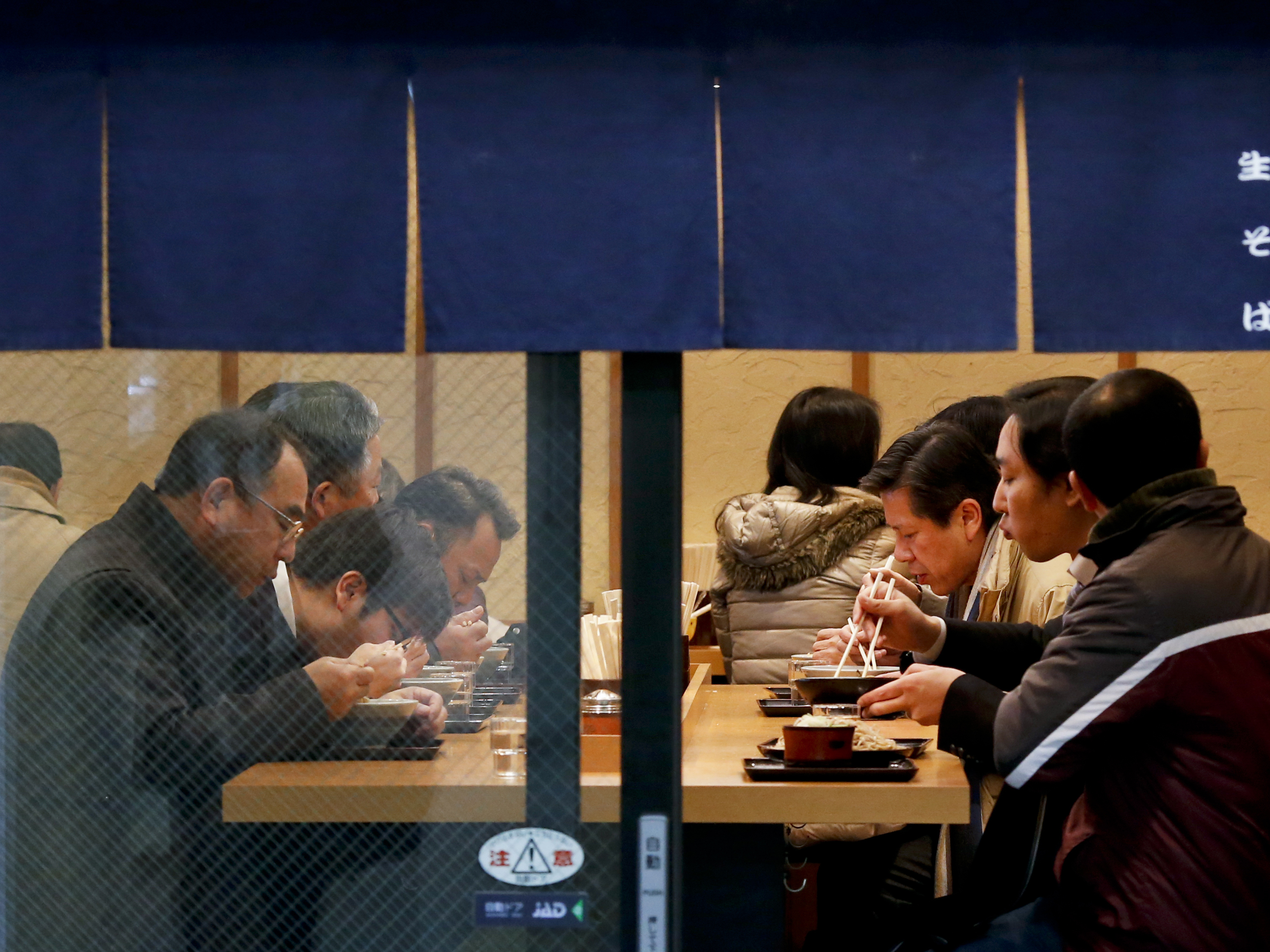 People slurp soup and pluck noodles at a soba and udon restaurant in Tokyo in February 2016. (Shuji Kajiyama/AP)