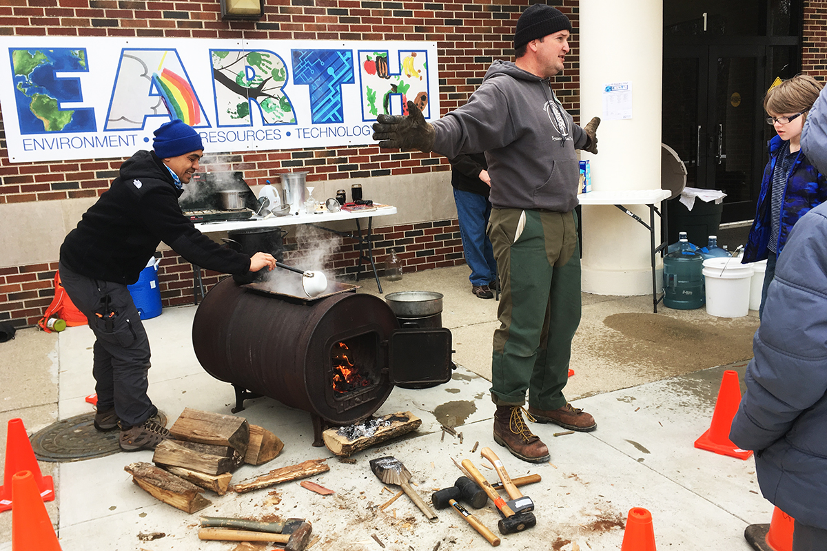 Shane Gibson (R), Director of Environmental Education for Sycamore Land trust talks to students about maple syrup in front of his converted barrel stove. Neil Kintanar(L), outdoor educator with Bradford Woods ladles warm sap from the pan for students to taste (Alex Chambers/WFIU)