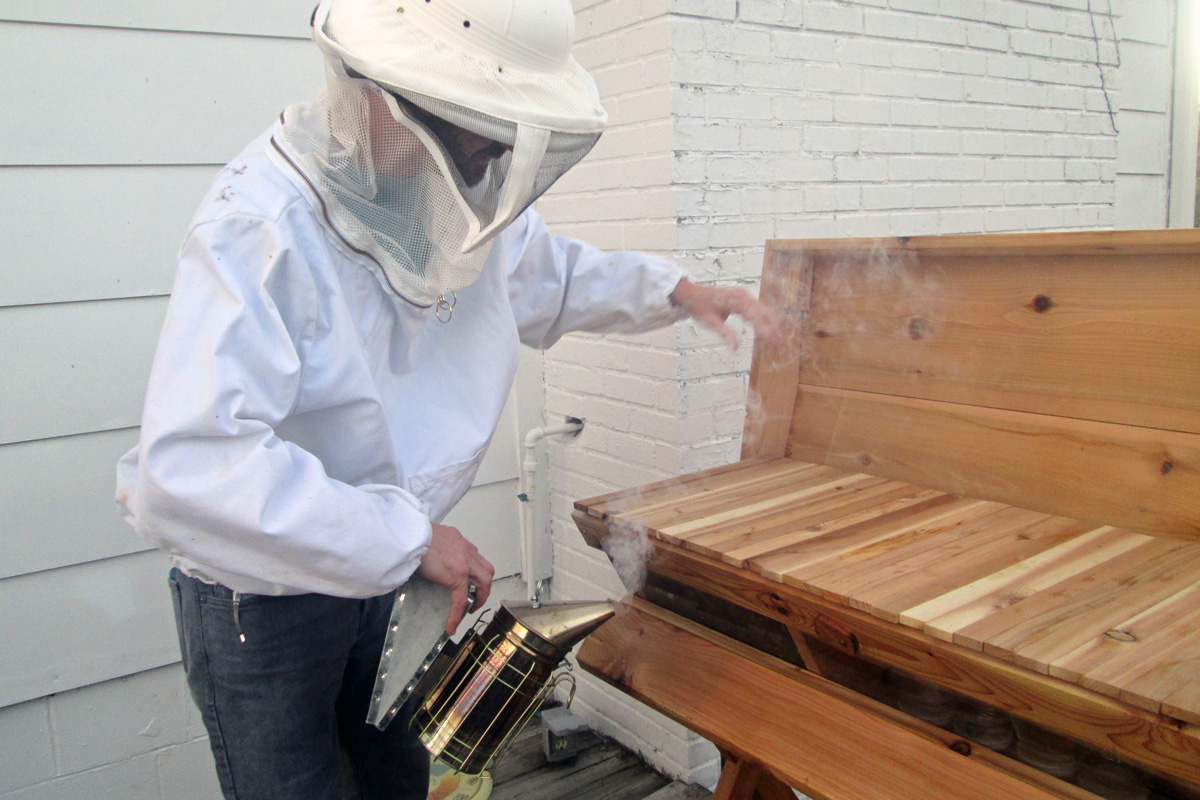Mike has suited up in protective gear before opening the hive and smoking the bees (Annie Corrigan/WFIU)