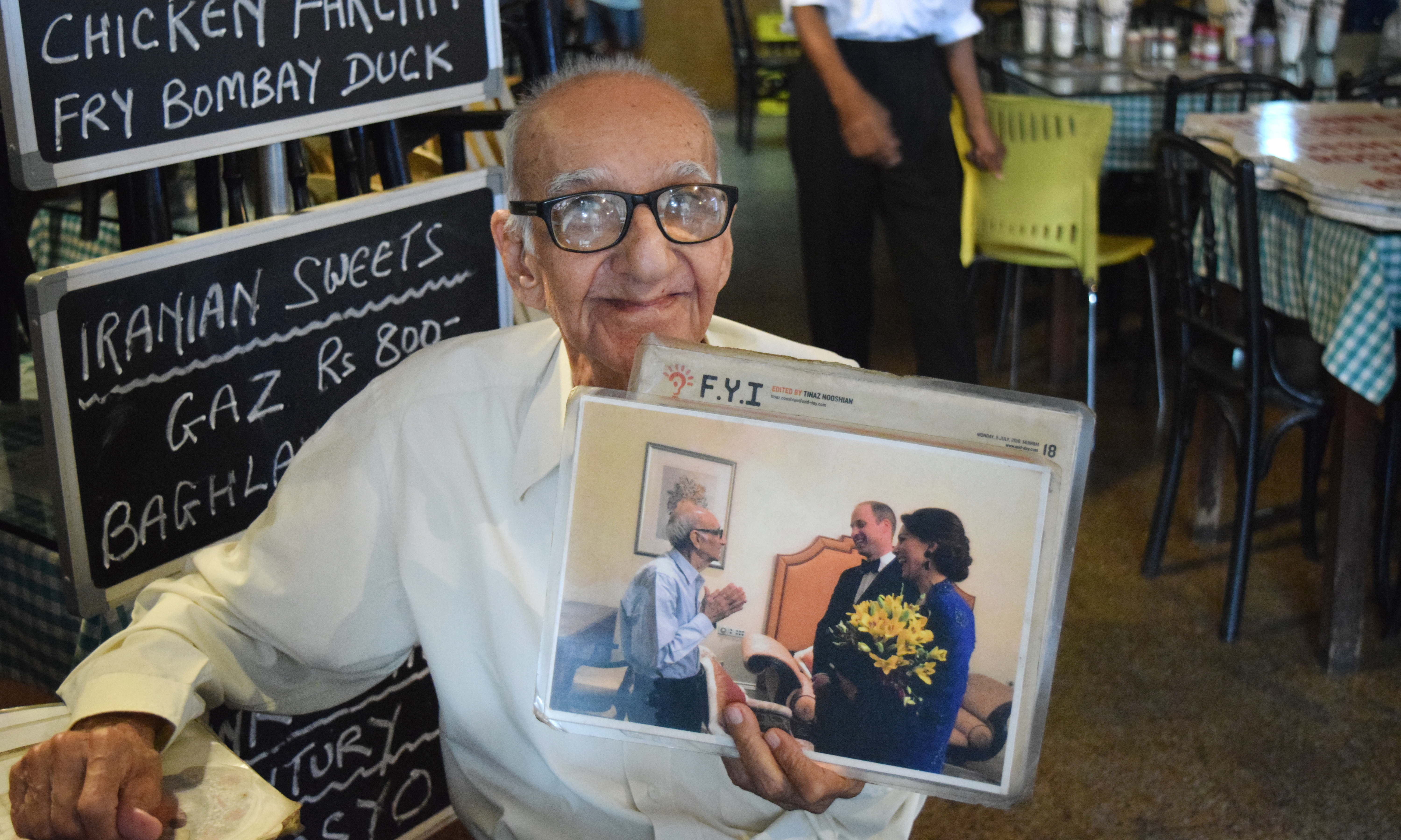 Boman Kohinoor, 97, has spent the past eight decades committed to his beloved Britannia & Co., one of Mumbai's last Parsi cafes. Here, he proudly holds up a photo of himself with two members of the British royal family: the Duke and Duchess of Cambridge, Prince William and the former Kate Middleton. (Rebecca Rosman for NPR)