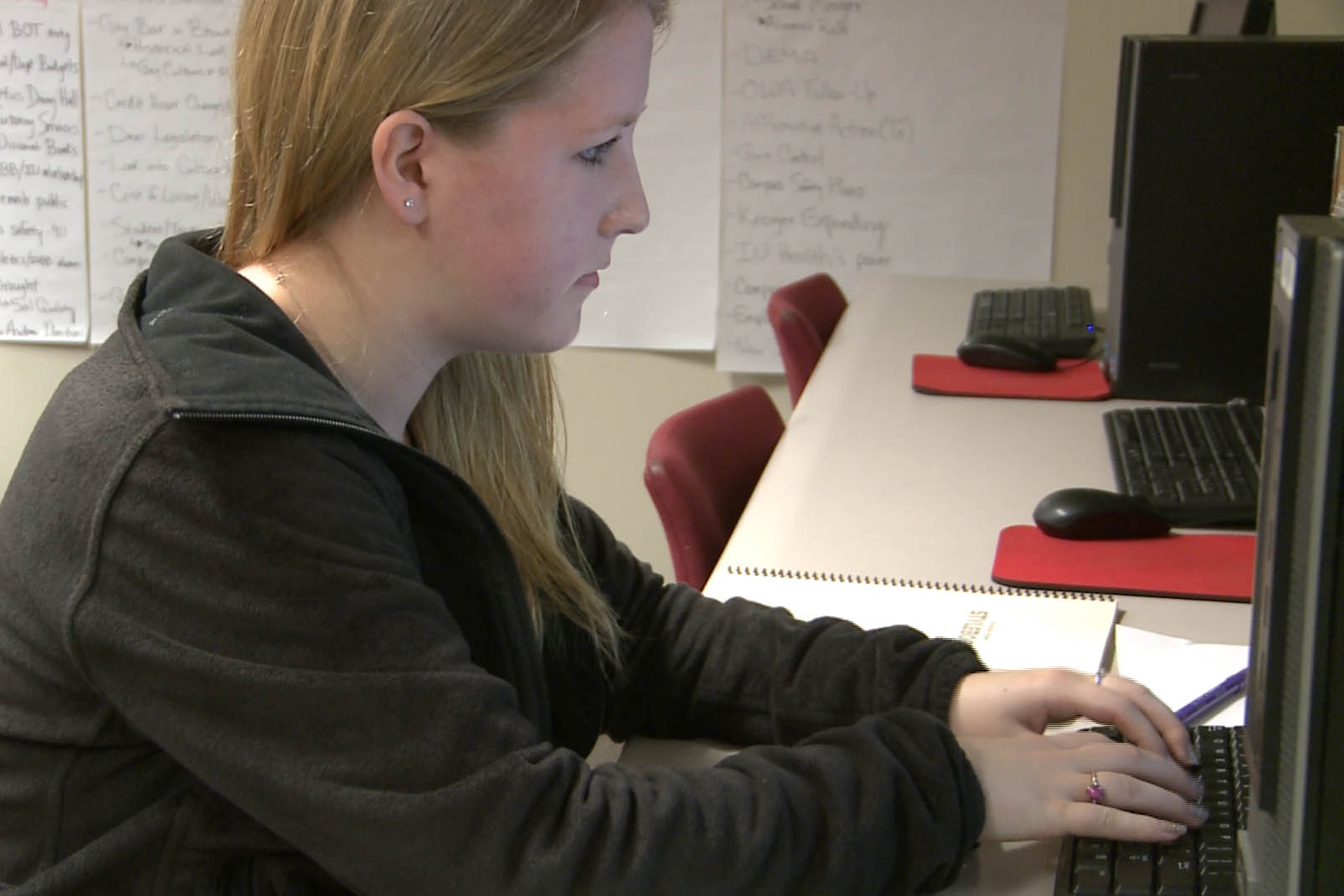 A student journalist works on a story for a college paper.
