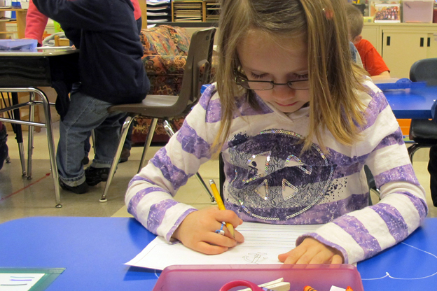 A kindergartener at East Side Elementary in Brazil practices writing.