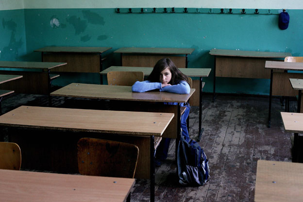 A pupil leans on her desk in an empty classroom