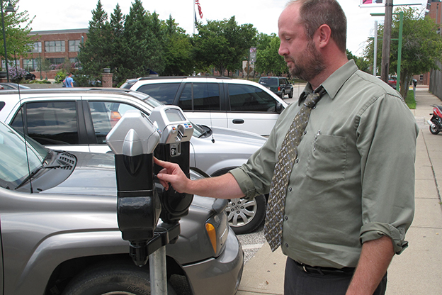 Bloomington local Jason Meredith inserts coins to the parking meter on Morton Street.