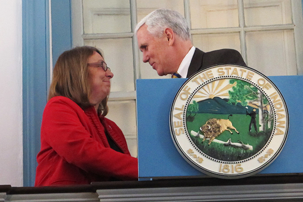 Rep. Rhonda Rhoads, R-Corydon, shakes Gov. Mike Pence's hand as he takes the podium for a speech at Indiana's first state capitol building.