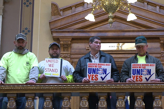 Protesters hold up signs in the statehouse