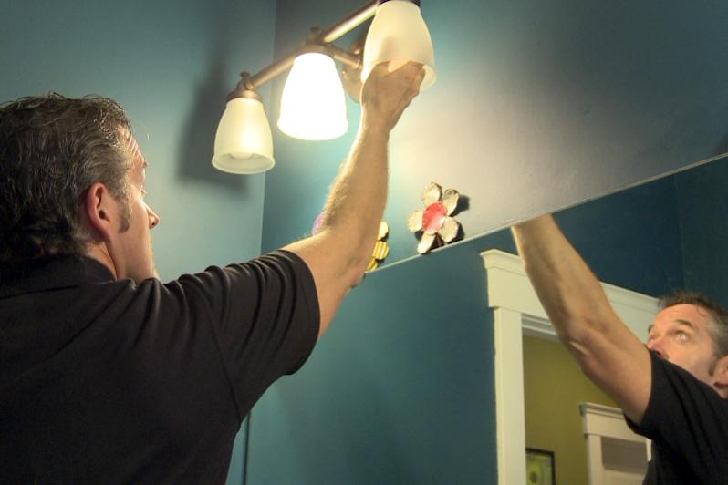 Mike Bass changes a light bulb