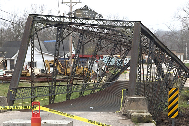 A damaged iron bridge behind caution tape.