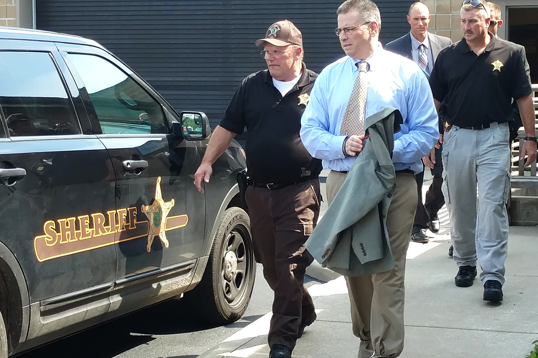 Daniel Messel, shackled, is escorted to the Sheriff's vehicle after he looked at his vehicle with the jurors.