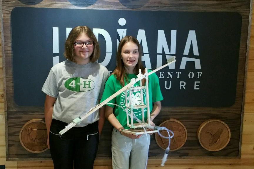 Haylee Drake, left, and Maddie Gearld show off their Clay County 4-H fluid dynamics project.