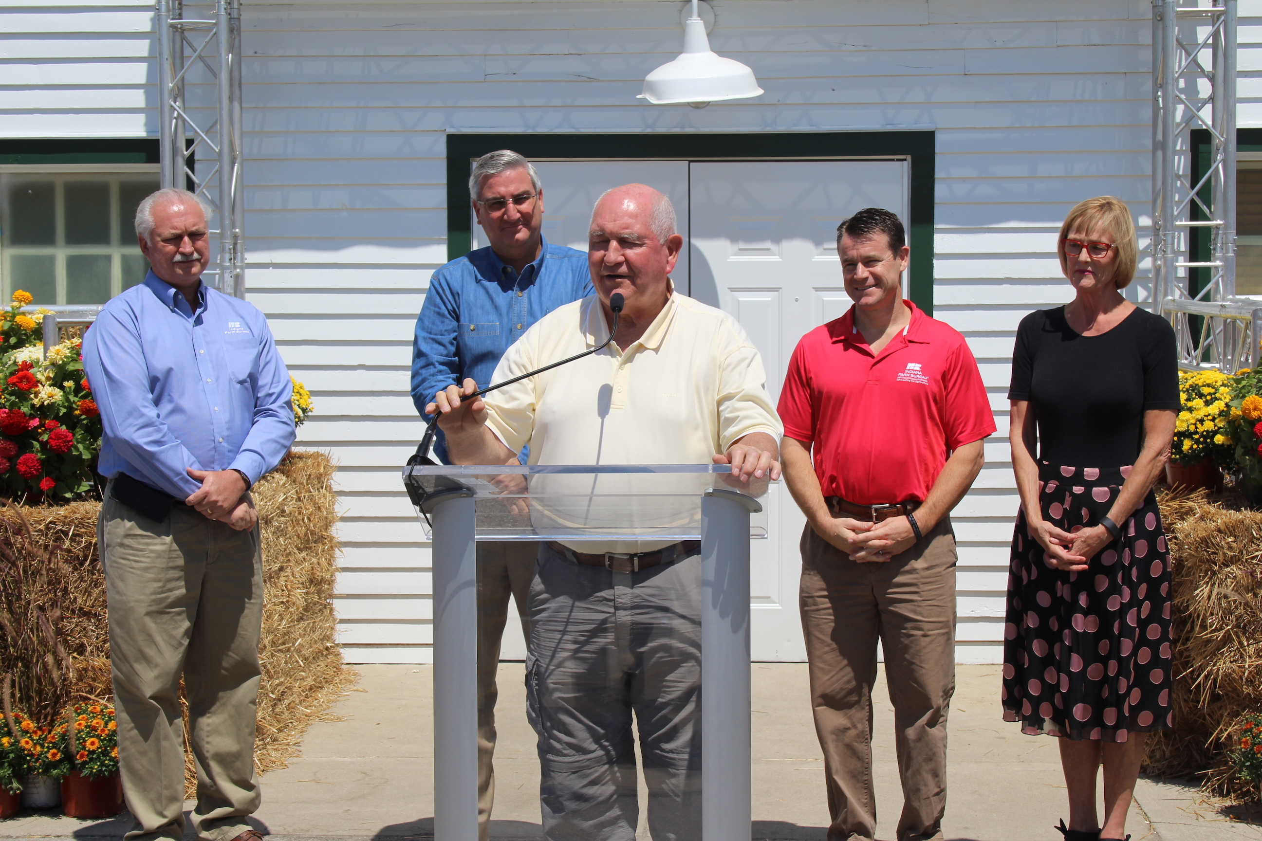 U.S. Secretary of Agriculture Sonny Perdue speaks alongside Indiana Farm Bureau President Randy Kron, Gov. Eric Holcomb, Sen. Todd Young (R-Ind.) and Lt. Gov. Suzanne Crouch at the Indiana State Fair.