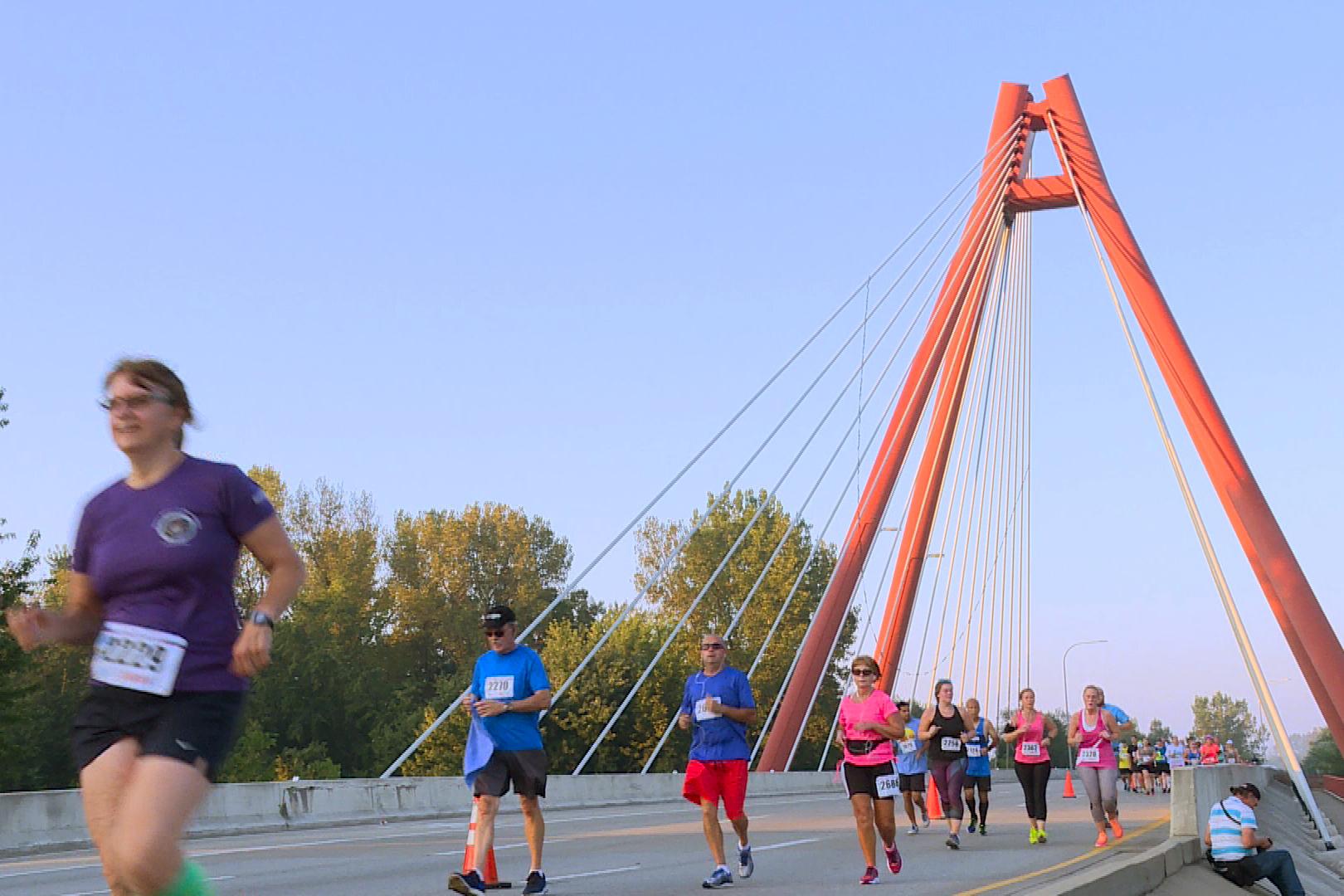 Dozens of runners cross a bridge during the Mill Race Marathon in Columbus Indiana.